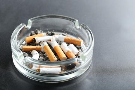papel filtro: Las colillas de cigarrillo con la ceniza en el cenicero sobre fondo negro Foto de archivo