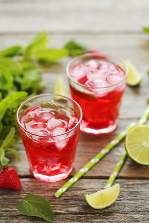 Fresh strawberry drink in glass with lime on wooden table Stock Photo