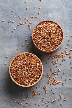 brown flax: Brown flax seeds on grey wooden table Stock Photo