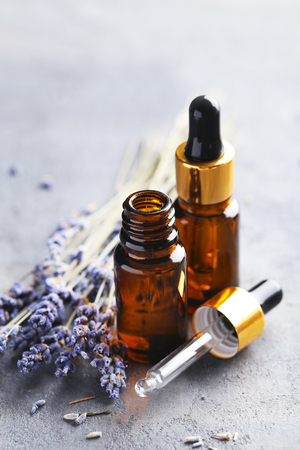 lavender oil: Lavender oil and flowers on grey table Stock Photo