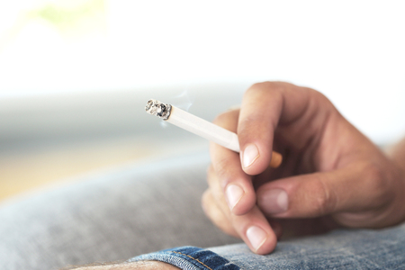 Male hand holding a cigarette Stock Photo