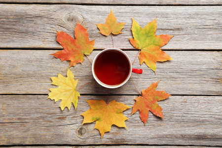 calendario octubre: Autumn leafs with cup of tea on grey wooden table