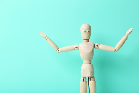 proportions of man: Wooden figure with googly eyes on a green background