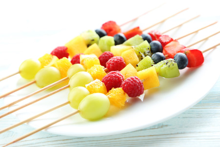 brochetas de frutas: Fresh fruit on skewers on a white wooden table