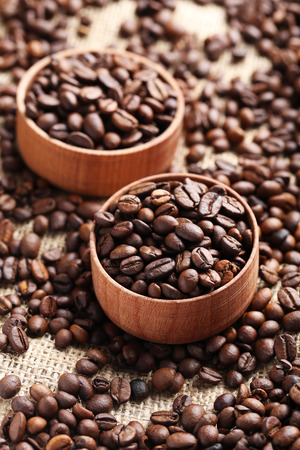 grained: Brown roasted coffee beans in bowl on sackcloth Stock Photo