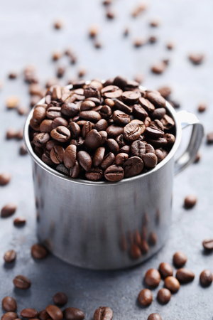 Roasted coffee beans in mug on grey table