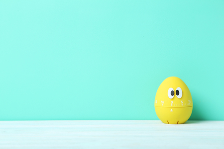 Yellow egg timer with googly eyes on a green background Stock Photo