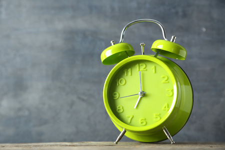 Green alarm clock on a grey wooden table