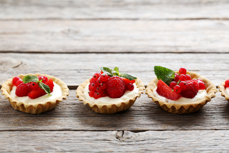 Dessert tartlets with berries on grey wooden background