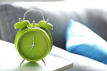 bedside: Green alarm clock on white bedside table