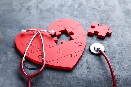 Corazón rojo del rompecabezas con el estetoscopio en el fondo de madera gris Foto de archivo - 68171289
