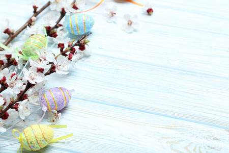 Tree branches with flowers and easter eggs on blue wooden table
