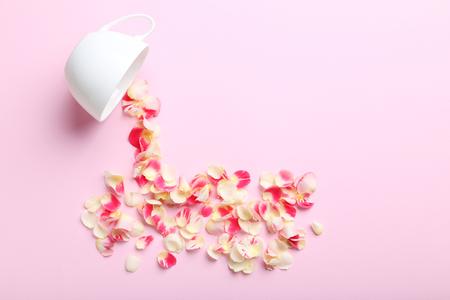 Rosenblätter und weiße Tasse auf einem rosa Hintergrund