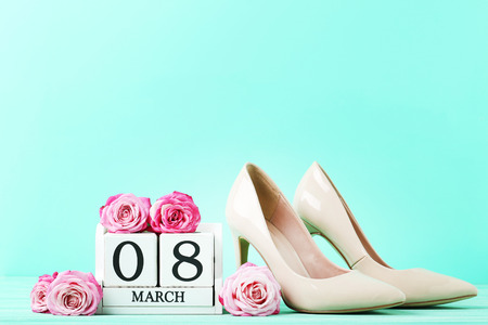 Pink roses with cube calendar and high-heeled shoes on green background Stock Photo