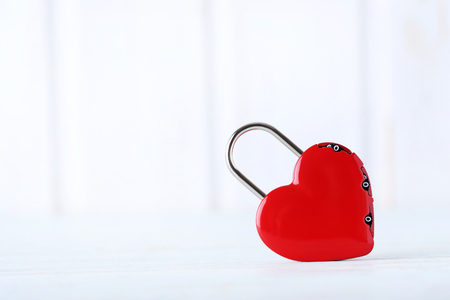 lockout: Heart shaped padlock on white wooden table Stock Photo