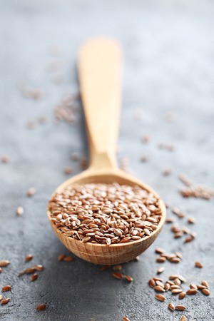 linseed: Brown flax seeds on grey wooden table Stock Photo