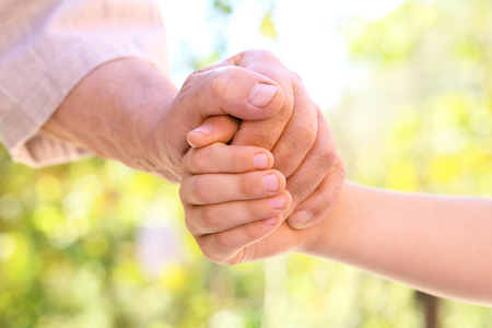 puckered: Hands of young child and old senior Stock Photo