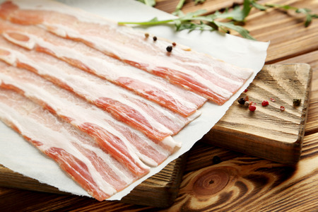 Crispy strips of bacon on a brown wooden background Stock Photo