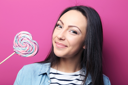 Young woman with lollipop on pink background Stock Photo