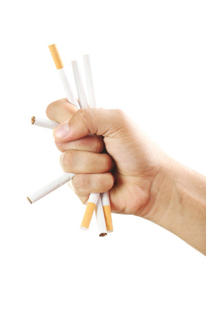 toxic substance: Male hand crushing cigarettes on white background