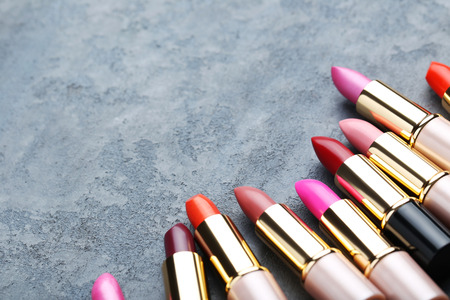 Colorful lipsticks on grey wooden table