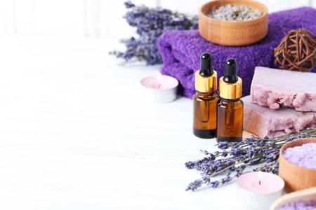 L'huile de lavande avec du savon et de fleurs sur blanc table en bois