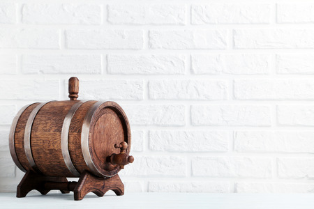 Wooden barrel with iron rings on brick wall background Stock Photo