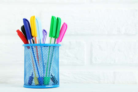 highlighter pen: Colored pens in basket on brick wall background Stock Photo