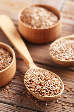 Brown flax seeds on a wooden table Stock Photo