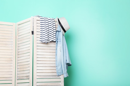 screen partition: Clothes hanging on folding screen on a green background