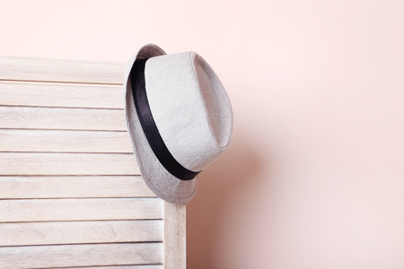 screen partition: Hat hanging on wooden folding screen on a beige background