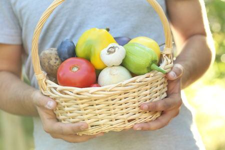 Man holding in hands basket with fruits and vegetables