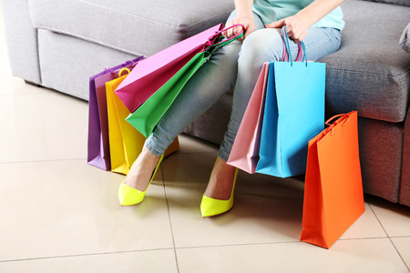 furniture store: Female legs with yellow high heels and shopping bags on grey sofa