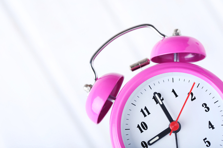 Pink alarm clock on a white background