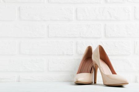 Paia delle scarpe a tacco alto delle donne su un fondo del muro di mattoni