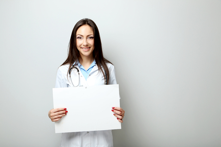 Portrait of young medical doctor with sheet on blank paper on a grey background Stock Photo