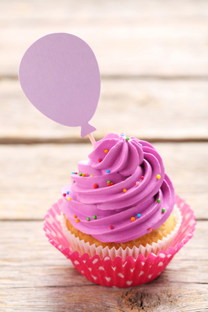 Tasty cupcake on a grey wooden table
