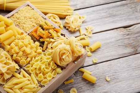 macarrones: Diferentes tipos de pasta en la mesa de madera gris