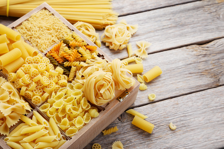 uncooked: Different kinds of pasta on grey wooden table
