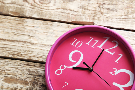 oclock: Pink round clock on a grey wooden table