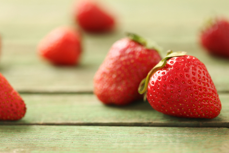 Fresh and tasty strawberries on a green wooden table