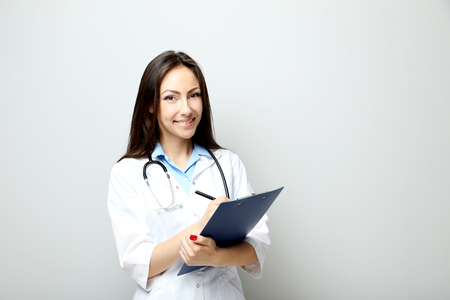 Portrait of young medical doctor with clipboard on a grey background