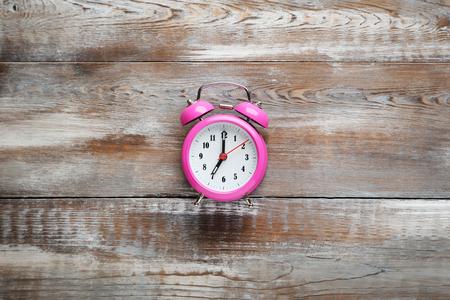 alarmclock: Pink alarm clock on brown wooden table