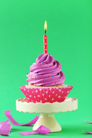 Tasty cupcake with candles on a green background