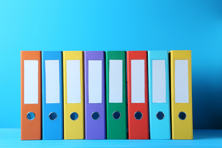 Colorful office folders on blue background