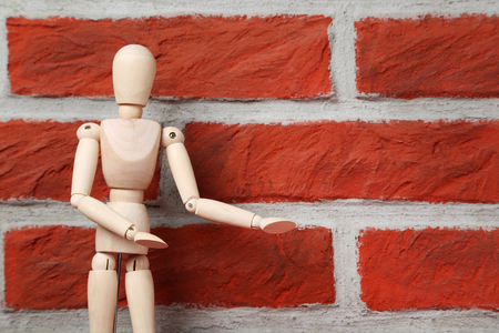 Wooden figure on a brick wall background Stock Photo