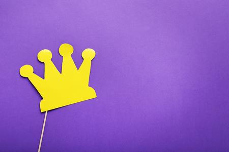 紫色の背景に棒で黄色紙の王冠