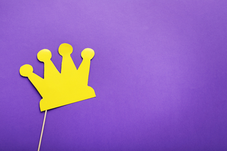 Yellow paper crown on stick on purple background
