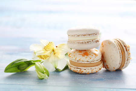 French macarons with alstroemeria on blue wooden table Stock Photo