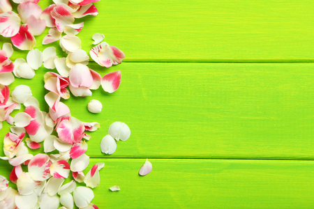 Rose petals on green wooden table